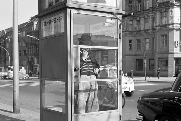 Kurfürstendamm in Berlin-Halensee. Bild zeigt einen Mann mit Hut in einer Telefonzelle.