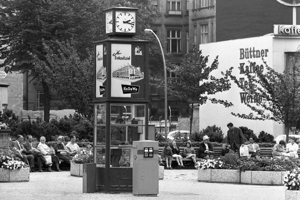 Platz in Berlin Charlottenburg. Bild zeigt einen Briefkasten, einen Mann in einer Telefonzelle, eine KaDeWe Werbung und das Cafe Büttner (Kaffee, Tee, Weine).