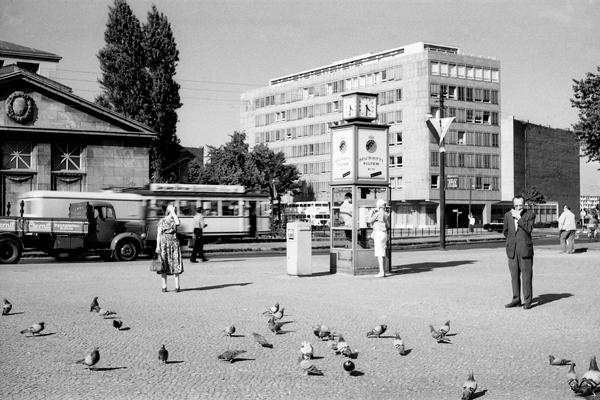 Wittenbergplatz in Berlin. Bild zeigt Tauben, einen Mann mit Zigarette, ein Frau mit Kleid, Tasche und Hand vor dem Gesicht, eine Telefonzelle, Briefkasten und im Hintergrund Autos und ein Hochhaus.