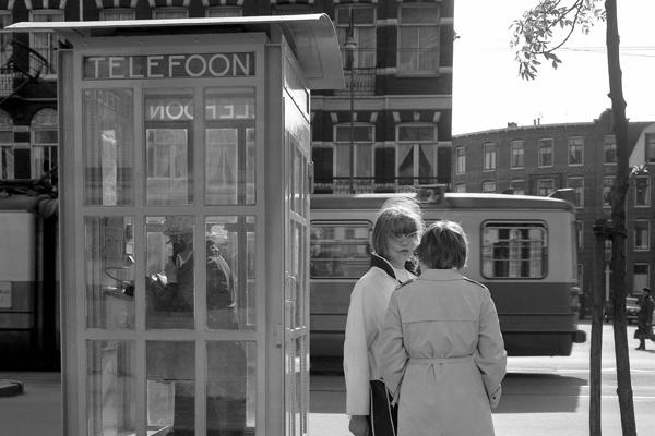 Eine ältere Dame telefoniert in einer Telefonzelle in Amsterdam und junge Frauen vor der Telefonzelle unterhalten sich.