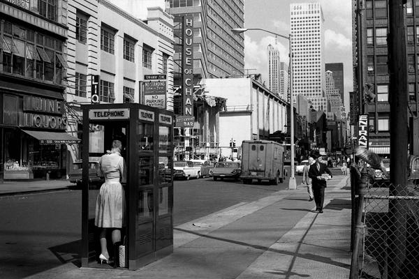 Eine Frau telefoniert in einer Telefonkabine an der Fifth Avenue. Im Hintergrund das Bürogebäude 666 Fifth Avenue. Sie trägt ein modisches Kleid.