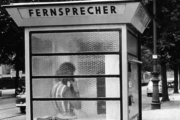 Eine junge Frau im gestreiften Kleid ist durch die Ornamentglasscheiben einer Telefonzelle auf der Suarez-Hauptstraße in Berlin zu sehen.