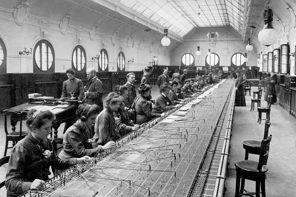 Telefonistinnen arbeiten an einem langen Tisch in einem Fernsprechamt in Berlin, einem sogenannten Tischamt.