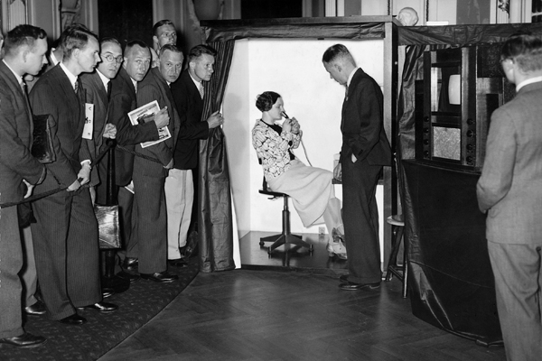 Im Rahmen der 37. Jahrestagung des Verbandes Deutscher Elektrotechniker (VDE) 1935 in Hamburg zeigte die Reichspost zum ersten Mal sog. 'Gegenfernsehsprechen'. In der Fernsehsprechzelle sitzt eine junge Hamburger Schauspielerin, deren Bild ebenso dem Gesprächspartner übertragen wird wie der Ton.