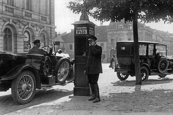 Ein Chauffeur telefoniert an einer neu errrichteten Anrufsäule für Autofahrer in Potsdam. Links ein Wagen der Marke Mercedes.