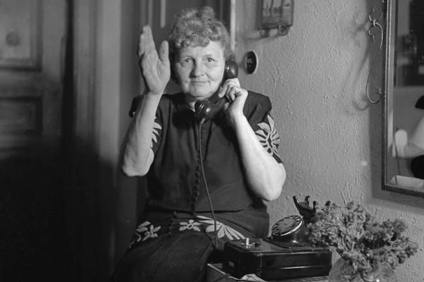 Eine Fraue telefoniert und winkt dem Fotografen.