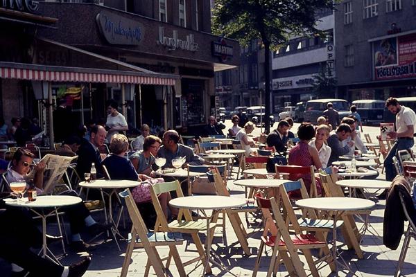 Menschen vor dem Cafe Möhring am Kurfürstendamm in Berlin und im Hintergrund ein Mann mit einem Spiegel mit Hakenkreuz.