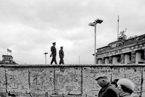 Grenzbeamte der Deutschen Demokratischen Republik auf der mit Graffiti bemalten Mauer vor dem Brandenburger Tor.