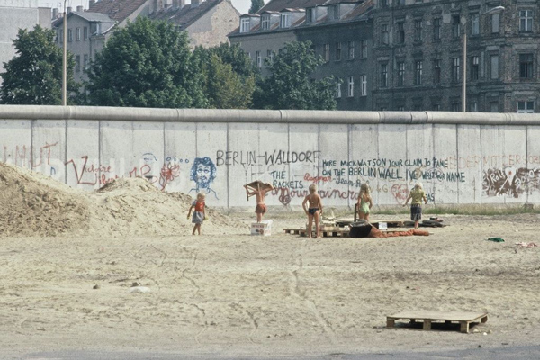 Kinder in Badekleidung spielen an einem Sandhaufen vor der mit Graffiti bemalten Berliner Mauer.