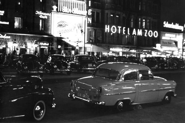 Blick auf das Hotel am Zoo am Kurfürstendamm nahe der Joachimstaler Straße am Abend mit Neonreklamen und davor parkende Autos auf dem Mittelstreifen und am Straßenrand in Berlin.