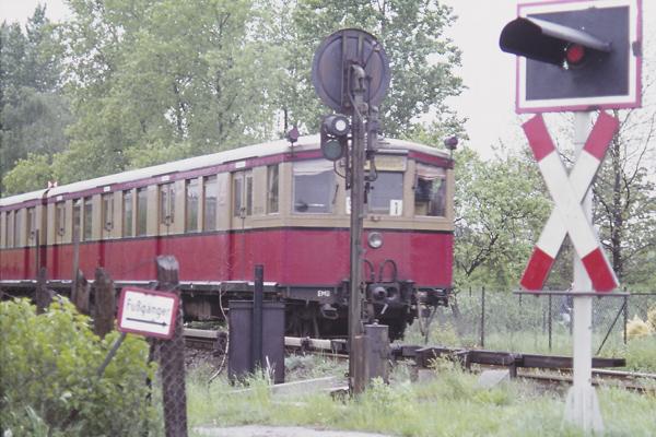 Das Bild zeigt einen Viertelzug bestehend aus Trieb und Beiwagen vom Typ 275 (Stadtbahn) auf dem Weg von Düppel (später Zehlendorf Süd) nach Zehlendorf. Die Strecke ist ein winziger Rest der Stammbahn, wie die ursprüngliche erste Eisenbahn in Preussen von Berlin nach Potsdam benannt wird. Ein anderes Teilstück wird noch von der Wanseebahn befahren. 1980 wurde der planmäßige Betrieb auf der Strecke Zehlendorf Düppel bis heute (2015) eingestellt. Der abgebildete Viertelzug ist ein sogenanntes Passviertel gewesen, also ein Viertelzug, welches zwar schon die Steuerleitungen für den Einmannbetrieb (EMB) eingebaut bekam, aber der Führerstand noch nicht dafür eingerichtet wurde. Passviertel deshalb, weil er in Zugverbände mit Einmannbetriebsfahrzeugen eingefügt (eingepasst) werden konnte.