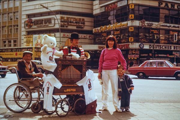 Eine Mutter und ihr Kind posieren neben einem Leierkastenmann und einem Kriegsinvaliden während einer Städtereise in Westberlin für ein Foto.
