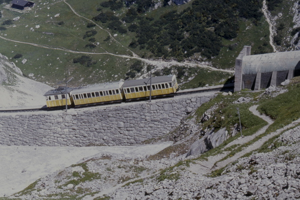 Ein gelber Zug der Wendelsteinbahn vor der Einfahrt in einen Tunnel in den Bergen.