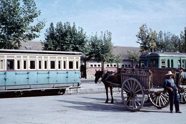 Kleinunternehmer mit Maultierkarren warten auf Kundschaft an einem Bahnhof mit altem Personenwagen und einem Triebwagen.