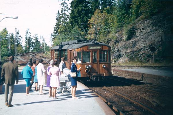 Bahnreisende warten auf die einfahrende Lok.