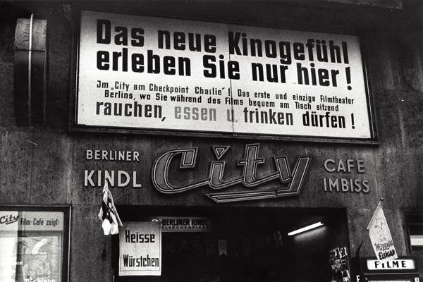 """Werbeplakat des Berliner City-Kinos am Checkpoint Charlie. Unten links das Filmplakat zum Film """"Die blaue Hand""""."""