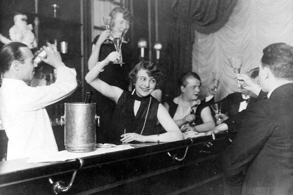 Gäste an der Theke einer Bar stoßen mit Sekt an.