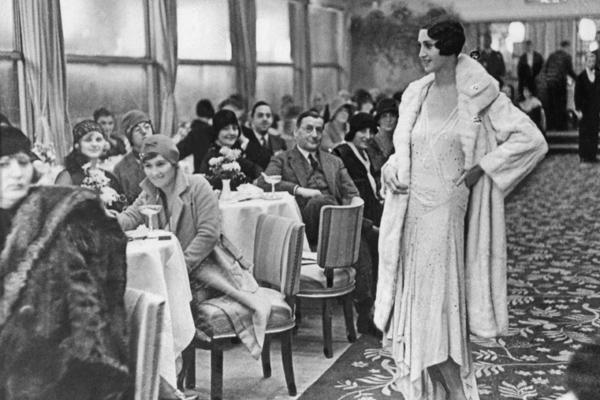 Ein Mannequin präsentiert ein Abendkleid mit Hermelinmantel auf einer Modenschau im Edenhotel in Berlin.