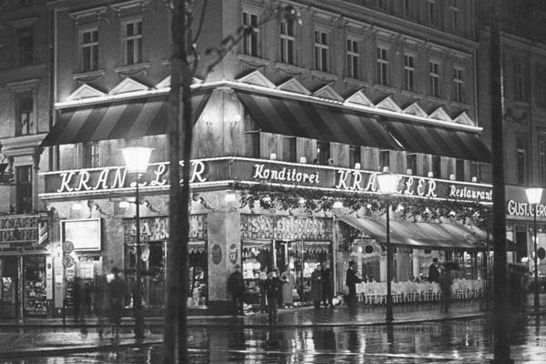 """Blick auf das Cafe Kranzler von der gegenüberliegenden Straßenseite aus.Das erste Café Kranzler in Berlin wurde 1825 von Johann Georg Kranzler als eine kleine Konditorei in der Straße """"Unter den Linden"""" in Berlin Mitte eröffnet. 1932 öffnete die zweite Filiale im ehemaligen Cafe des Westens unter dem Namen """"Restaurant und Konditorei Kranzler"""" an der Joachimstaler Straße (heute Joachimsthaler Straße) im Bezirk Carlottenburg. Beide Gebäude wurden in den Jahren 1944 und 1945 bei Luftangriffen zerstört."""