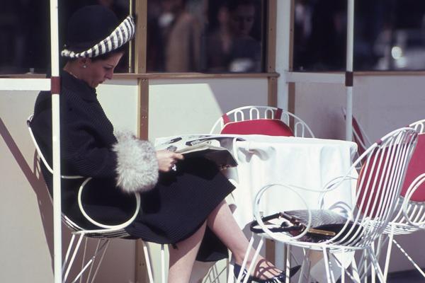 Dame sitzt im Cafe Kranzler auf dem Kurfürstendamm in Berlin und liest.