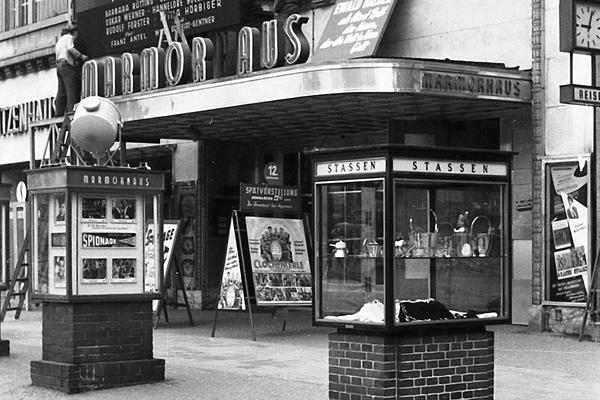 Berlin: Kino Marmorhaus am Kurfürstendamm. Bild zeigt Vitrinen (Stassen) und Männer die ein Filmplakat (Spionage) aufhängen.