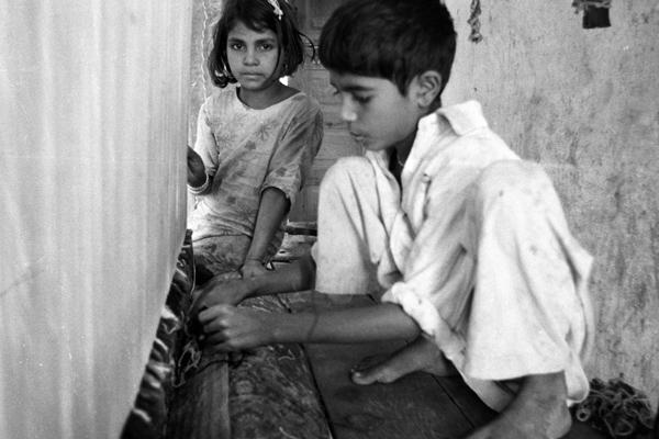 Ein Junge knüpft einen Teppich. Die kleine Schwester schaut ihm dabei zu.