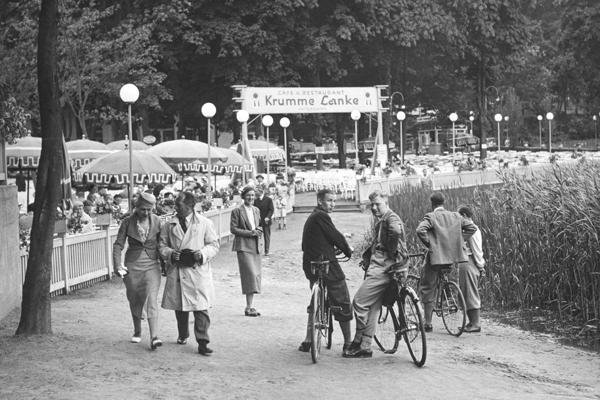 """Das Ausflugslokal """"Krumme Lanke"""" in Berlin. Zu sehen sind einige Besucher auf dem Weg vor dem Eingang, sowie drei Radfahrer."""