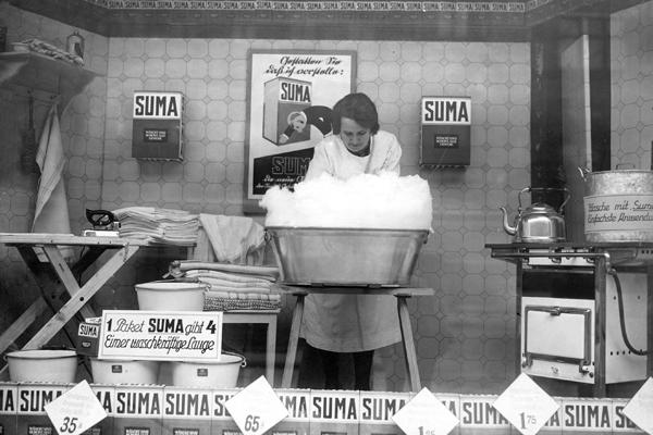 Als Werbeaktion wäscht eine Frau mit dem Waschmittel 'Suma' in der Öffentlichkeit Wäsche.