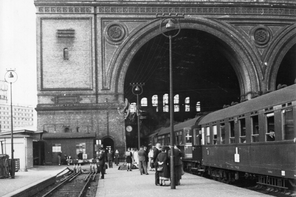 Passagiere stehen vor einem D-Zug mit herabgelassenen Fenstern vor der Abfahrt in Richtung Süden an einem Gleis im 1880 fertig gestellten Anhalter Bahnhof in Berlin.