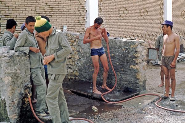Junger Mann duscht sich bei Soldaten am Rande der Salzwüste Chott el-Jerid, Tunesien