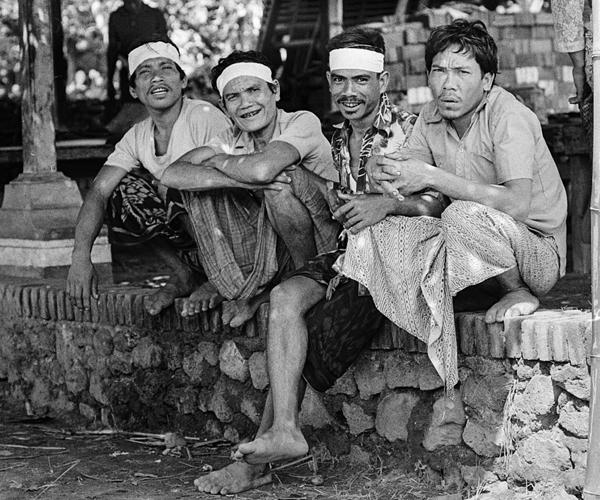 in ihren traditionellen Sarong sitzen die vier Balinesen spitzbübisch auf einer Mauer .