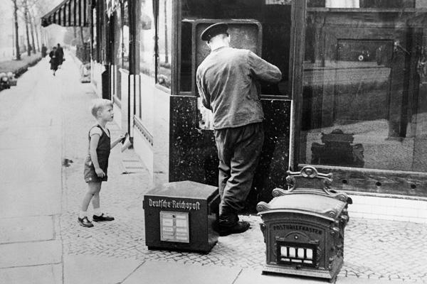 Der alte verschnörkelte 'Postbriefkasten' wird durch einen neuen Kasten der 'Deutschen Reichspost' ersetzt.