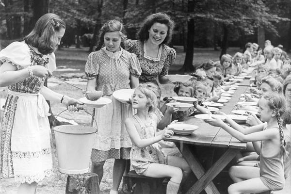 In den Schulferien erhalten Kinder Suppe. Während die Mütter in Fabriken arbeiteten, werden die Kinder zentral versorgt.
