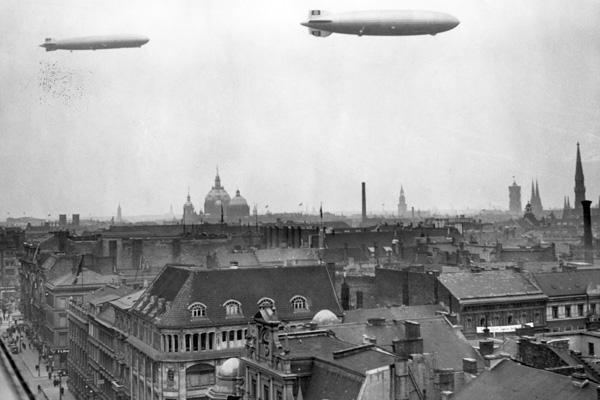 """Blick vom Verlagshaus des Scherl-Verlags in Richtung Berliner  Dom. Über der Stadt schweben die Luftschiffe LZ 129 """"Hindenburg"""" und LZ 127 """"Graf Zeppelin""""."""
