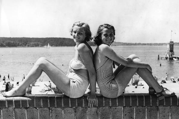 Zwei junge Frauen posieren auf einer Mauer am Strandbad Wannsee in der Sonne. Im Hintergrund liegt der von Badegästen bevölkerte Sandstrand.