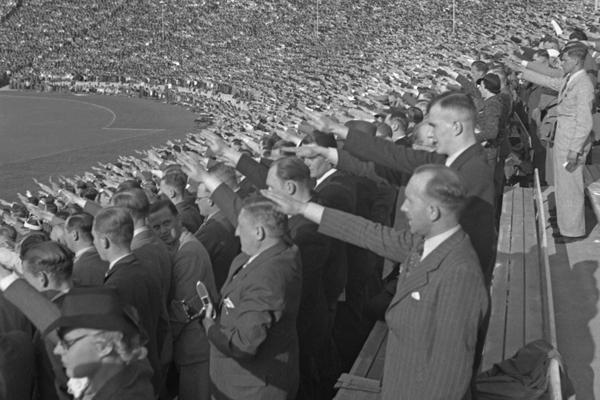 Aufnahme von Zuschauern im Berliner Olympiastadion während eines Fußballspiels (vermutlich der deutschen Nationalmannschaft) der XI. Olympischen Sommerspiele der Neuzeit im August 1936. Die Zuschauer in der Südkurve des Stadions recken ihre Arme zum Hitlergruß. Im Hintergrund ist die Westkurve mit der Anzeigetafel zu sehen. Auf dem Gebäude wehen Hakenkreuzfahnen.