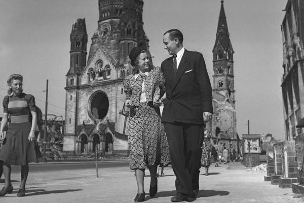 Verliebtes Paar schlendert durch die Stadt in Berlin-Charlottenburg, hinter ihnen die Kaiser-Wilhelm-Gedächtniskirche.