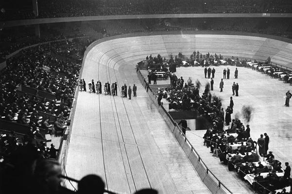 Blick auf die Radrennbahn und die Zuschauerränge in der Berliner Deutschlandhalle, im Rahmen eines Omnium Rennens. Auf der Bahn stehen einige Rennradfahrer und ihre Helfer für den Start eines Punkterennens bereit.