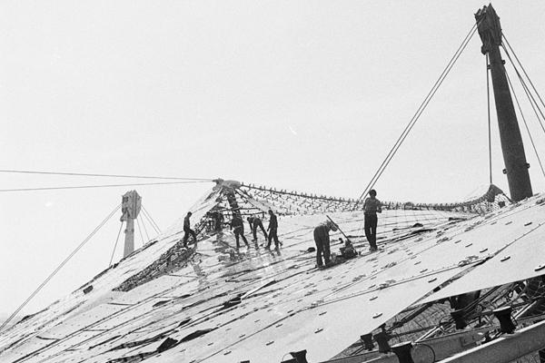 Arbeiter montieren Platten auf dem Münchner Olympistadion.