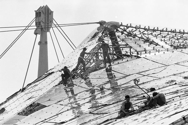 Arbeiter montieren Platten auf dem Münchner Olympiastadion.