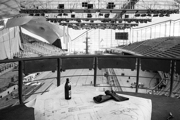 Bierflasche, Arbeiterhandschuhe und ein Lage-/Bauplan vor der noch nicht fertiggestellten Olympiaschwimmhalle.