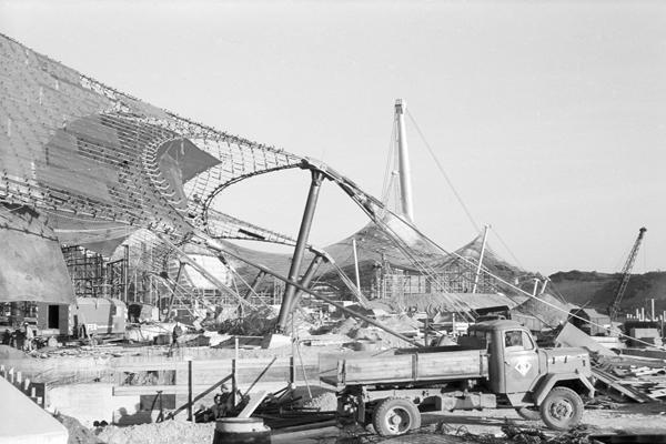 Bau des Schwimmstadions. Ein Teil der Plexiglasplatten ist bereits auf dem Dach angebracht.