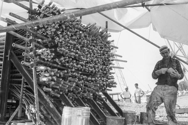 Fundament der Masten mit Enden der Verspannungen. Ein Maler streicht gerade die Drahtenden zum Schutz gegen Korrosion an.