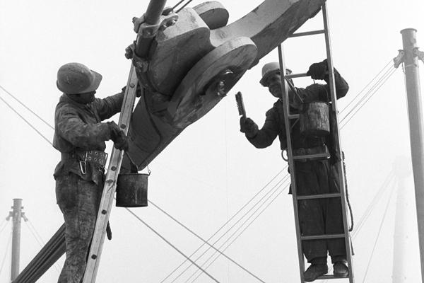 Maler in Arbeitskleidung und mit Helm stehen auf Leitern und bearbeiten die Spannteile des Seilnetzes des Münchner Olympiadaches mit Bürsten, Pinsel und Farbe