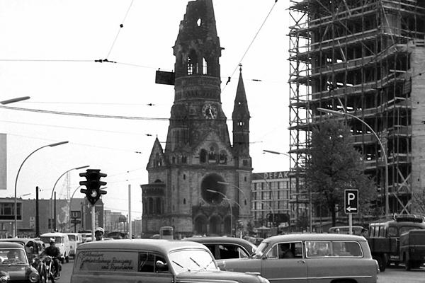 Hardenbergstraße und Kaiser Wilhelm Gedächtnis Kirche in Berlin. Im Vordergrund Autos und eine Ruine mit Baugerüst.