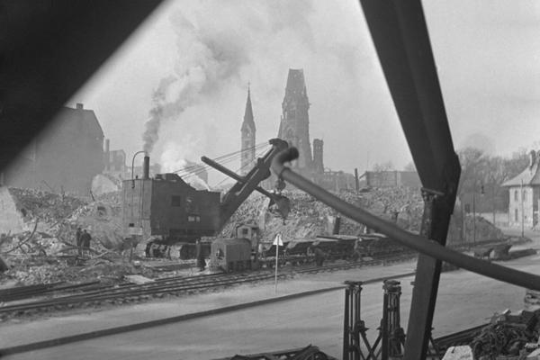 Undatierte Aufnahme eines Baggers beim Abtragen eines Schutthaufens und beladens von Loren mit Trümmerteilen vor einem teilweise durch Bomben zerstörtem Wohnblock in der Nähe des Kurfürstendamms im Stadtteil Charlottenburg in Westberlin, Britische Besatzungzone. Die dieselbetriebene Baumaschine nimmt die Trümmer mit einem Schürfkübel auf. Eine Schmalspurdiesellok zieht die Loren. Im Hintergrund ist der Turm (Hohler Zahn) der der Ruine der Kaiser-Wilhelm-Gedächtniskirche zu sehen.