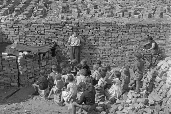 Undatierte Aufnahme einer Gruppe von Kindern die zwischen Stapeln aus den Trümmern geborgener Ziegel einem Puppenspiel zuschauen. Als Verkleidung des Puppentheaters dienen Ziegel. Rechts neben der Bühne steht der Puppenspieler. Im Hintergrund sind weitere Ziegelstapel, eine vorbeifahrende Straßenbahn (Tram) sowie teilweise durch Bomben zerstörte Häuser zu sehen.