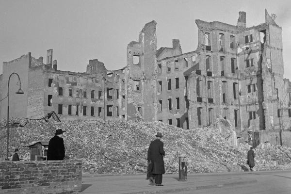 Undatierte Aufnahme von Fußgängern vor Häusergerippen in Berlin, vermutlich Westberlin, 1950. Die durch Bomben zestörten Wohnhäuser sind teilweise eingestürzt. Neben dem Gehsteig befinden sich Trümmerhaufen.