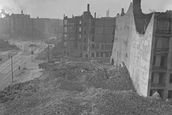 Undatierte Aufnahme eines Trümmerhaufens in Berlin, vermutlich Westberlin, 1950. Rechts und im Hintergrund sind Häusergerippe zu sehen. Links ist eine Straße zu sehen. Am hinteren Ende des eingestürzten Wohnblocks steht ein Lastwagen. Hier wird mit der Entrümmerung begonnen.