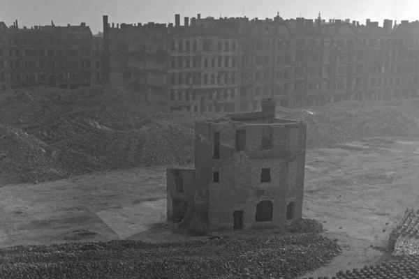Undatierte Aufnahme einer fast vollständig enttrümmerten Brachfläche in Berlin, vermutlich Westberlin, 1950. Auf der Fläche wurden abgeklopfte Ziegel für den Bau von neuen Häusern aufgestapelt. In der Mitte steht ein teilweise zerstörter Teil eines Wohnhauses. Im Vordergrund ist eien Straße mit vorbeifahrenden Autos zu sehen. Im Hintergrund: zerstörte Wohnblöcke.